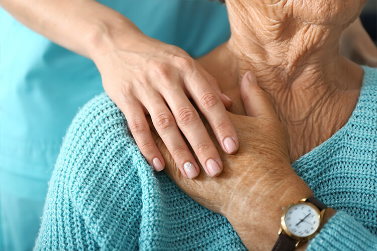 Nurse hand on elderly hand